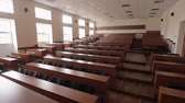 mikrofon : Panoramic view of empty lecture hall. Auditorium with brown rows of wooden desks. Black padded chairs. Blackboard. Tribune with microphone. Large, bright windows.