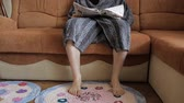 газета : Young white man in the bathrobe sits on the sofa and starts reading a journal. Bare feet stamp on the spliced rug.