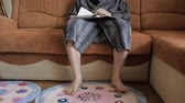 газета : Young man in bathrobe sitting on the sofa and reading a journal. His hand turn over the page of the newspaper and bare feet gently stamp.