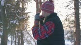 tricotar : guy in winter clothes drinking hot mulled wine at sunset in winter forest, winter fun,slow mo