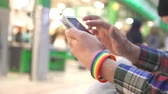 mens hands with an LGBT bracelet using a mobile phone