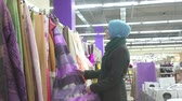 Muslim girl housewife in blue hijab and glasses selects fabrics at hardware store Stock mozgókép