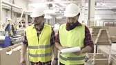 talkie : two workers in reflective waistcoats and helmets at the furniture factory