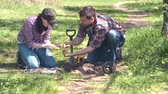 hunters : girl and man treasure Hunters digging up old coins found in the Park with metal detector Stock Footage