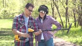 seeker : man treasure hunter explains to a girl how to use a metal detector