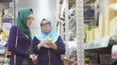 muslimah : beautiful mom and daughter muslim women shopping,discuss the goods Stock Footage