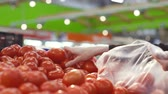 grocer : womens hands choose fresh juicy tomatoes in the supermarket