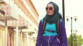 hijab : portrait of a girl tourist in a headscarf and sunglasses in a backpack