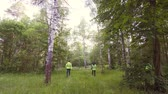 bandido : rescuers in green vests are searching for the missing child in the evening in the woods