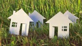 loutka : multiple cardboard house made of paper on green grass background Dostupné videozáznamy