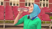 sportovkyně : Portrait of attractive muslim sports girl in hijab sitting drinking water