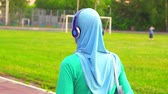 hijab : Attractive sporty muslim girl in hijab walks around the stadium and smiles at the camera Stock Footage