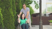 melhorar : young guy and a disabled girl in a wheelchair go for a walk Vídeos