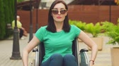 paraplegic : Portrait of an attractive disabled girl in a wheelchair looking at the camera,slow mo Stock Footage