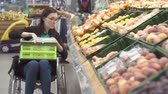 гандикап : Woman with a disability in a wheelchair shopping in the supermarket chooses fruits and puts them in a package. Стоковые видеозаписи
