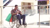 cadeira de rodas : A disabled man in a wheelchair using the phone in the Mall after shopping