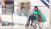 paraplegic : A disabled woman in a wheelchair using the phone in the Mall after shopping