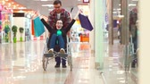 life support : A man is lucky after shopping a disabled woman in a wheelchair at the Mall.Theyre having fun, theyre laughing.Slow mo Stock Footage