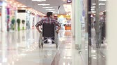 paraplegic : Man with a disability in a wheelchair going to the Mall Stock Footage