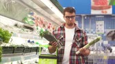 espinafre : A man with a basket is faced with a choice of what to buy in the Department with vegetables in the supermarket