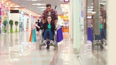 paraplegic : A man is lucky after shopping a disabled woman in a wheelchair at the Mall.Theyre having fun, theyre laughing. Stock Footage