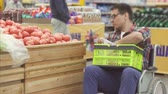 desamparado : Man with a disability in a wheelchair shopping in the supermarket chooses tomatoes and puts them in a package.close up