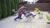 inválido : Man rolls a happy teenager in a wheelchair in the Park Vídeos