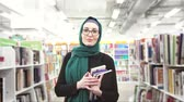 bibliotecario : girl in hijab with books in hands in library