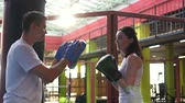 bokszolás : Woman boxer works out with trainer in the gym.Close up