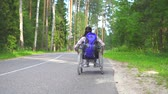 reforma : Disabled girl in a wheelchair traveler rides on the highway.Slow mo Archivo de Video
