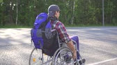 醫療保健 : Man with a disability in a wheelchair with a backpack traveling on the highway.Rear view.Slow mo