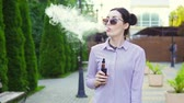 легкое : Portrait of stylish woman with shirt with electronic cigarette.Slow mo
