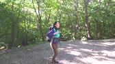 spacer : Girl tourist with a backpack up the trail in the woods,sun ray
