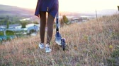 electric scooters : Girls legs goes and rolls the electric scooter next to the sunset sun,slow mo close up Stock Footage