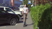 individualität : Young girl riding an electric scooter on the road in the city, slow mo