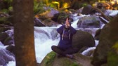 overcome : Girl sitting on a stone by the river and meditating,slow mo Stock Footage