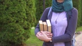 ders kitabı : Muslim girl student with books into the park ,slow mo