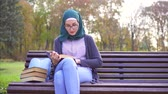 учебники : Cute student muslim girl in hijab reading a book on a bench at sunset