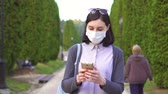 contagion : Pretty girl in a protective medical mask on her face in the park using the phone,slow mo