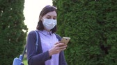 contagion : Girl in a protective medical mask on her face goes and uses the phone,slow mo