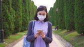 contagion : Pretty girl in a protective medical mask on her face in the park using the phone
