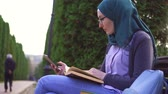 ders kitabı : Muslim student i engaged in learning with the help of phone and textbook Stok Video