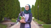 ders kitabı : Arab student in hijab with books goes to the park to study