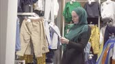 middle eastern ethnicity : Muslim woman in a hijab and a backpack chooses clothes in a childrens store