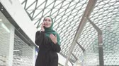 retailer : Pretty muslim woman in a hijab with a backpack goes to the shopping center and talks on the phone,slow mo