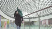 malaio : Pretty muslim woman in a hijab with a backpack and a medical mask on her face goes shopping,slow mo