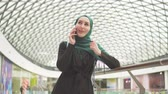retailer : Pretty muslim woman in a hijab with a backpack is standing in a shopping mall and talking on the phone