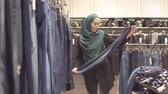 middle eastern ethnicity : Muslim woman in hijab and a backpack chooses jeans at the store in the mall
