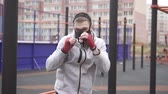vztek : Man in a training mask on his face boxing on a sports street playground,slow mo