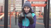 practising : Portrait of a boxer woman in boxing gloves on the street